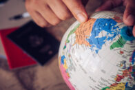 close-up-pointers-globe-tourists-are-planning-find-attractions-conception-travel_11304-1150